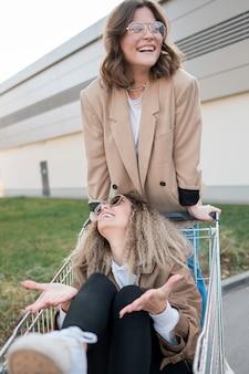 Vista frontal mujeres jóvenes jugando con carrito de compras