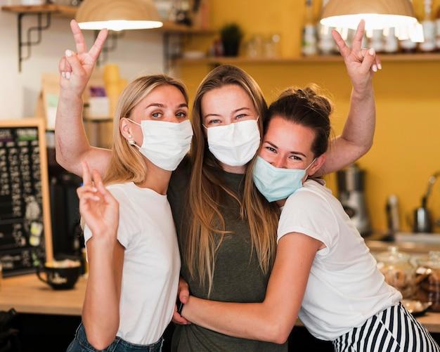 Vista frontal de las mujeres jóvenes con mascarilla