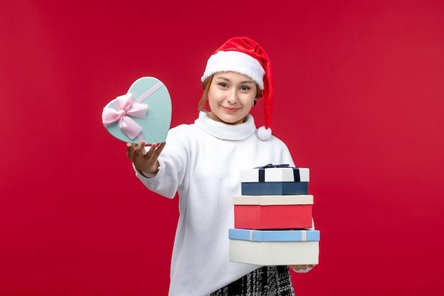 Vista frontal de las mujeres jóvenes con regalos de año nuevo en el escritorio rojo
