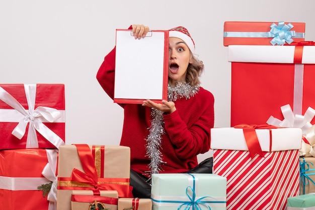 Vista frontal de las mujeres jóvenes sentados alrededor de regalos de navidad con nota