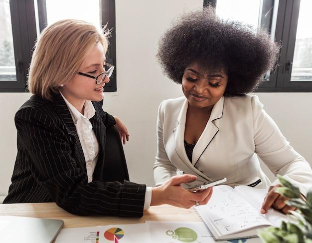 Vista frontal de mujeres de negocios en el escritorio