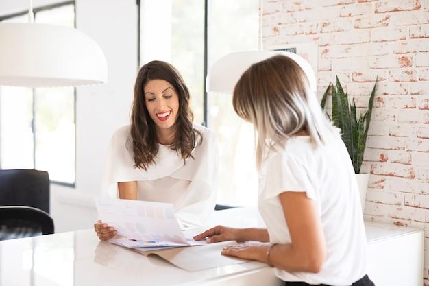 Vista frontal de mujeres en la oficina chateando