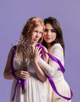 Vista frontal de mujeres posando con lavanda y cinta