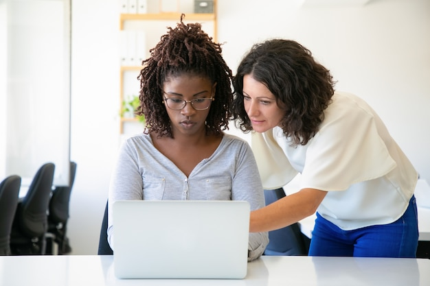 Vista frontal de mujeres seguras hablando mientras trabaja con la computadora portátil