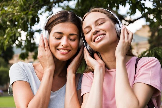 Vista frontal de mujeres sonrientes al aire libre escuchando música con auriculares
