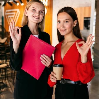 Vista frontal de las mujeres en el trabajo usando lenguaje de señas