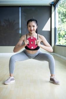 Vista frontal de mujeres en uniformes deportivos, pretendiendo ponerse en cuclillas y sostener pesas mientras está de pie en el gimnasio.