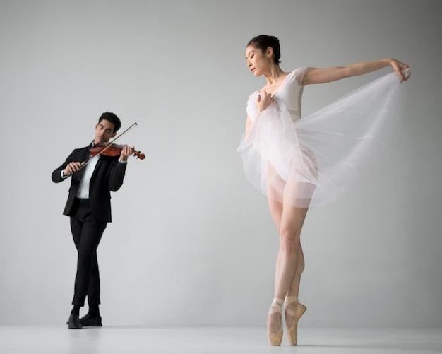 Vista frontal del músico de violín con bailarina