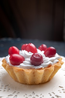 Vista frontal muy cercana delicioso pastel con crema y frutos rojos en la superficie oscura pastel galleta de frutas