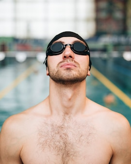 Vista frontal nadador masculino sosteniendo la cabeza