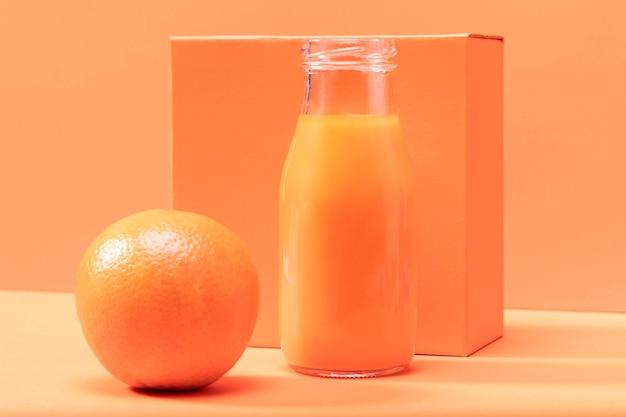 Vista frontal de naranja y batido en botella