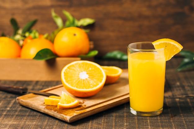 Vista frontal naranja a la mitad junto a jugo de naranja