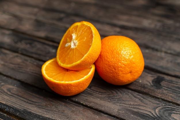 Vista frontal naranjas agrias frescas jugosas y suaves aisladas en el fondo rústico marrón