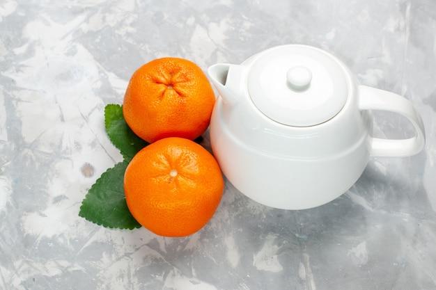 Vista frontal de naranjas frescas con hervidor sobre superficie blanca