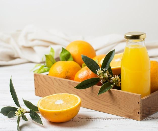 Vista frontal de naranjas y jugo en caja de madera.