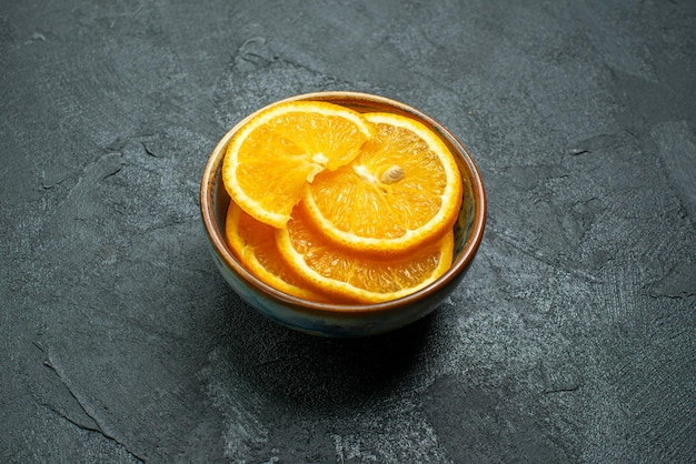 Vista frontal de las naranjas en rodajas frescas dentro de la placa sobre la superficie oscura de jugo de frutas tropicales exóticas cítricos