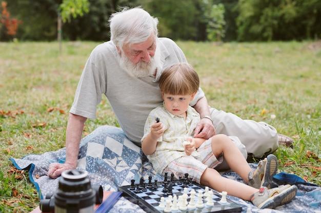 Vista frontal nieto sentado con el abuelo