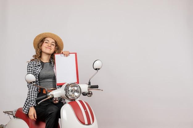 Vista frontal de la niña alegre viajero en ciclomotor con portapapeles rojo