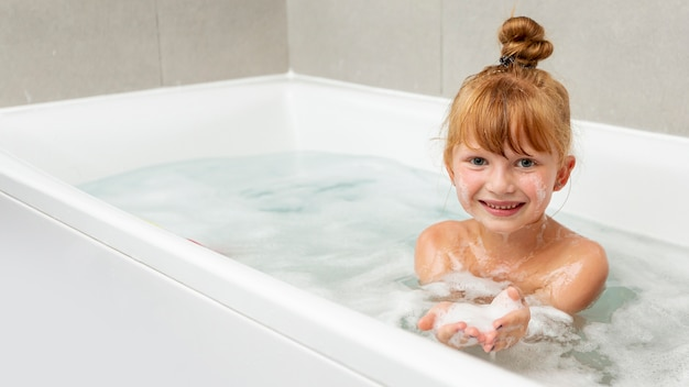 Vista frontal niña en la bañera