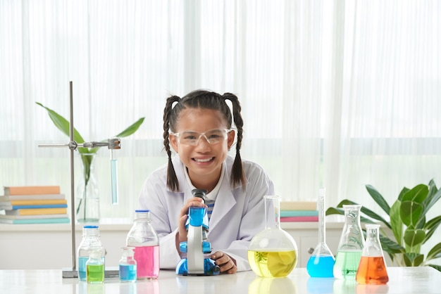 Vista frontal de la niña en bata de laboratorio haciendo el experimento químico