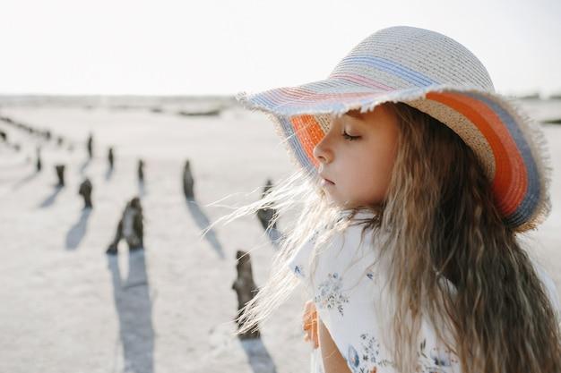 Vista frontal de una niña con cabello rubio vestida con el sombrero en la playa con los ojos cerrados