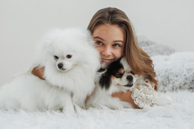 Vista frontal de niña y cachorros blancos lindos