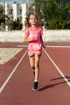Vista frontal de la niña en camiseta rosa corriendo
