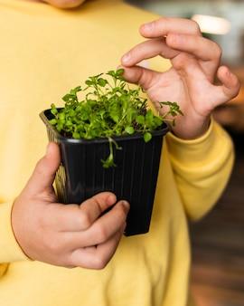 Vista frontal de la niña en casa con planta pequeña