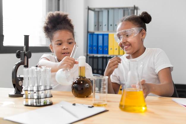 Vista frontal de la niña científica experimentando con química en casa