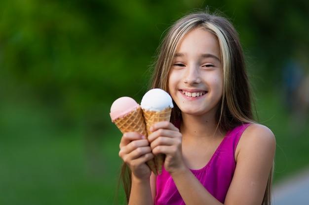 Vista frontal de la niña con conos de helado