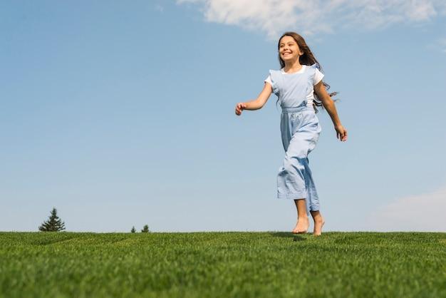 Vista frontal niña corriendo descalza sobre hierba