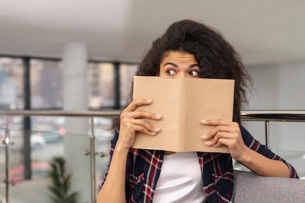 Vista frontal niña cubriéndose la cara con el libro