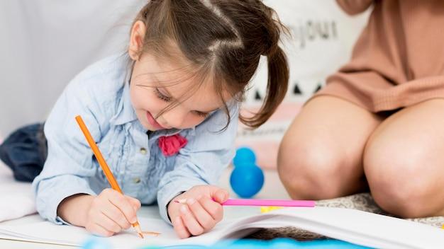 Vista frontal de la niña dibujando en casa