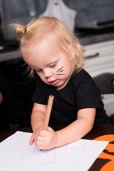 Vista frontal de la niña dibujando en la cocina