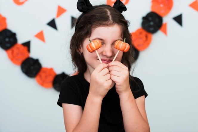 Vista frontal de una niña con dulces de calabaza