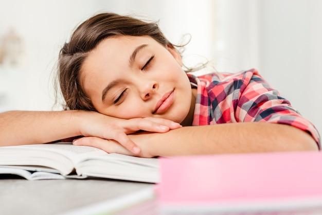 Vista frontal niña durmiendo en el libro