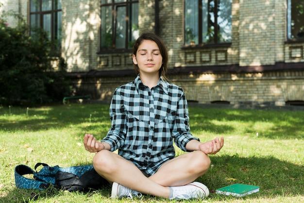 Vista frontal de la niña de la escuela secundaria meditando