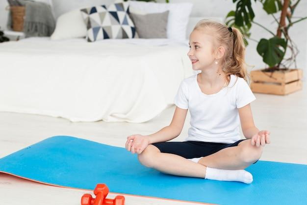 Vista frontal de la niña en la estera practicando yoga