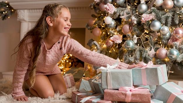 Vista frontal de la niña feliz con regalos y árbol de navidad