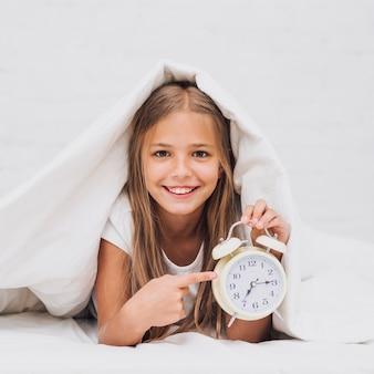 Vista frontal niña feliz señalando el reloj