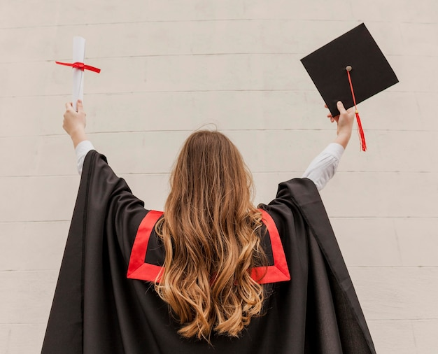 Vista frontal niña graduada con espalda