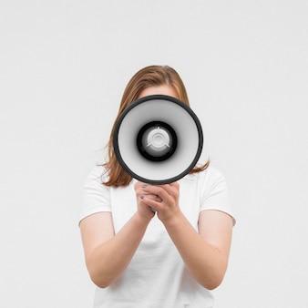 Vista frontal niña gritando en megáfono