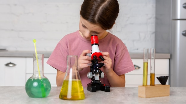 Vista frontal de la niña haciendo experimentos con microscopio y tubos de ensayo