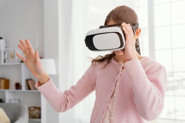 Vista frontal de la niña jugando con casco de realidad virtual
