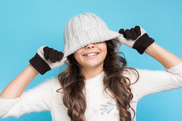 Vista frontal niña juguetona vistiendo ropa de invierno