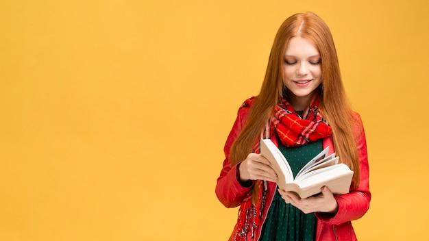Vista frontal niña leyendo libro