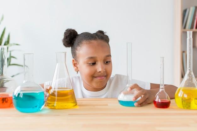 Vista frontal de la niña mirando los tubos de ensayo con pociones
