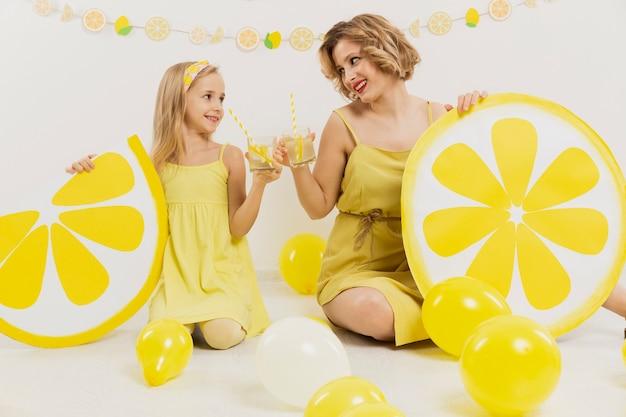 Vista frontal de niña y mujer brindando con limonada