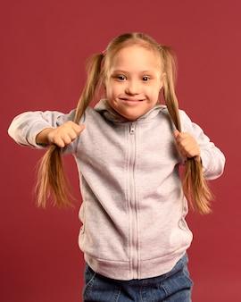 Vista frontal niña niña sosteniendo su cabello