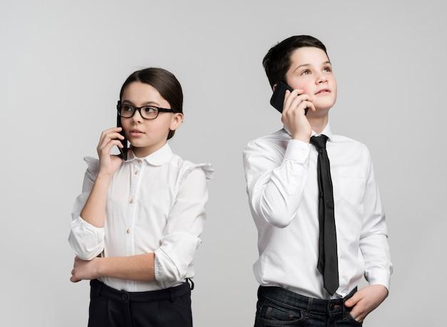 Vista frontal niña y niño hablando por teléfonos